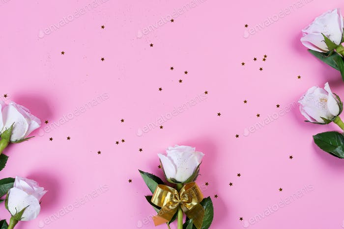 Pink roses flowers with gold bow and gold glitter on a pink background, flat lay