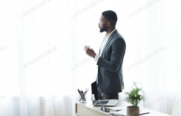 Thoughtful black businessman looking out of window and drinking coffee