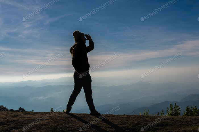 silhouette of a man who looking over the mountains landscape