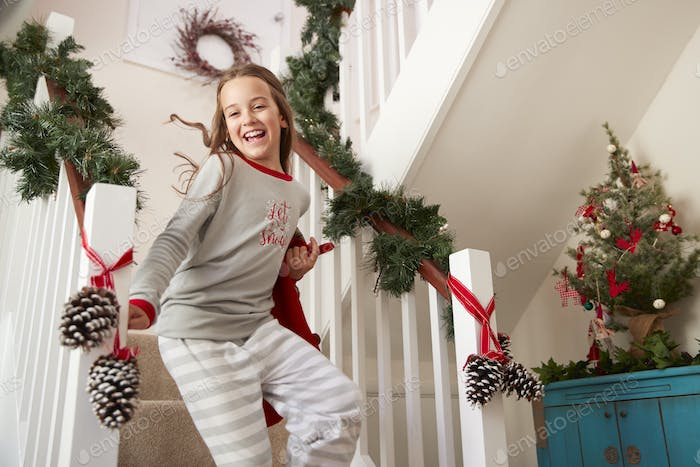 Excited Girl Wearing Pajamas Running Down Stairs Holding Stocking On Christmas Morning