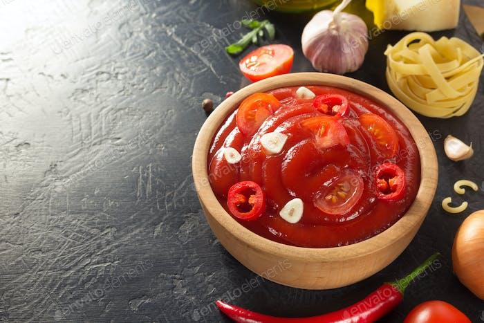 Tomatensauce in Schüssel auf schwarzem Hintergrund