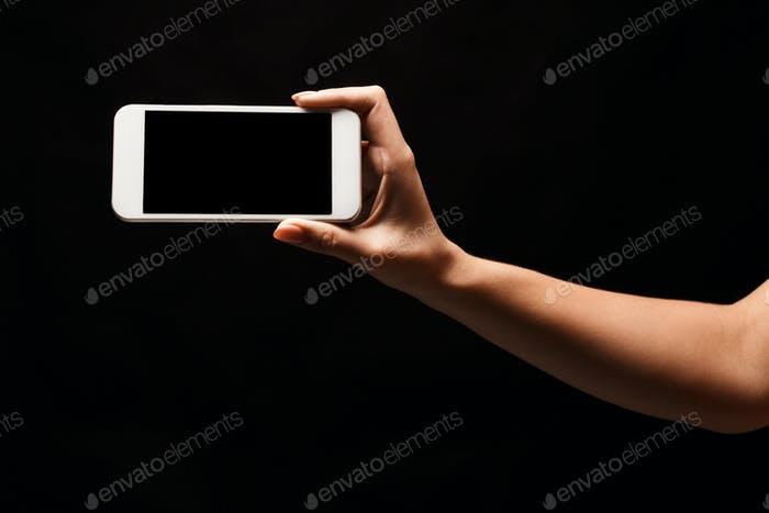 Female hand holding mobile smart phone with blank screen