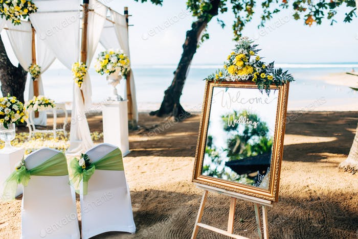 Wedding setting, beautiful and romantic ceremony decor on beach with waves background