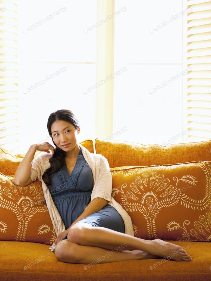 Asiatische Frau liegend auf Sofa