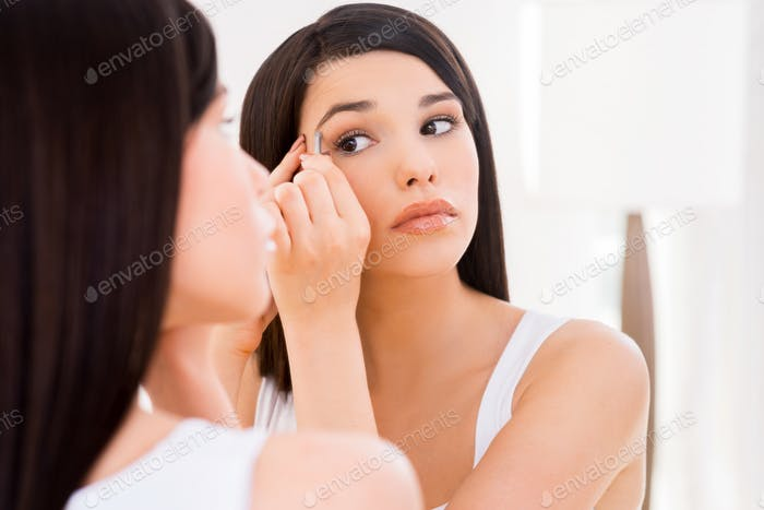 Woman tweezing eyebrows. Beautiful young woman tweezing eyebrows while looking at the mirror