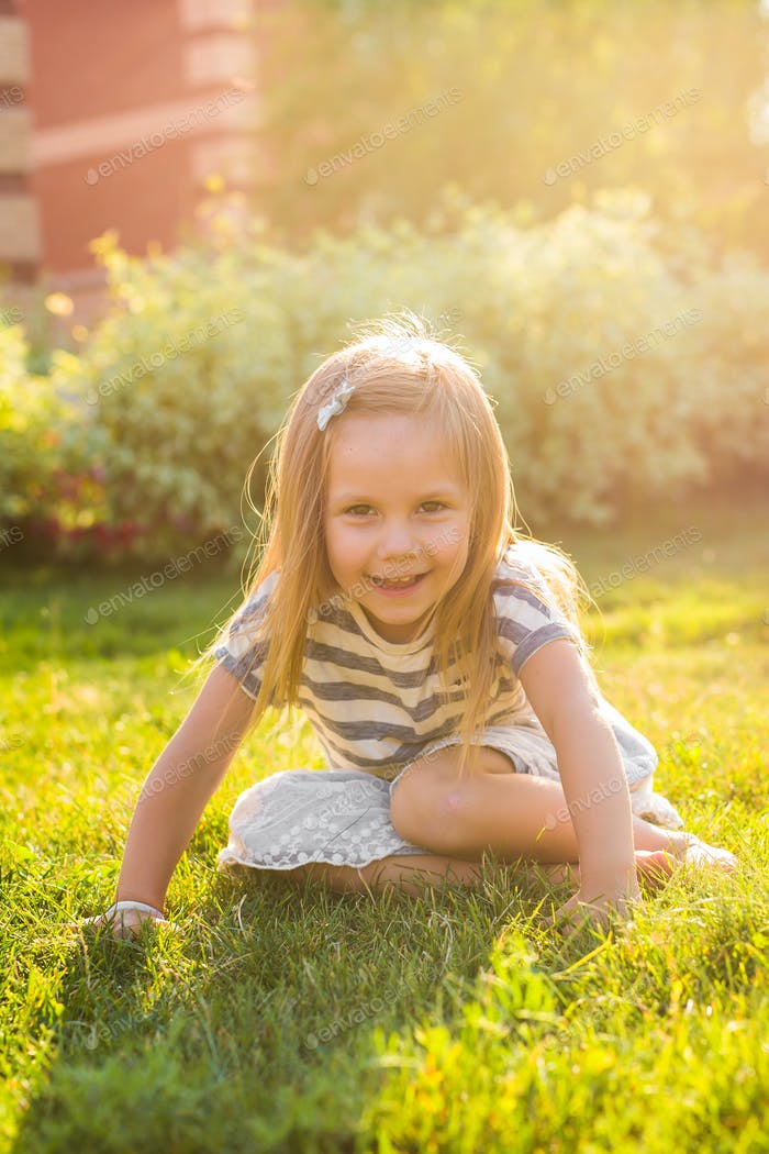Cute little girl on the meadow in spring or summer day