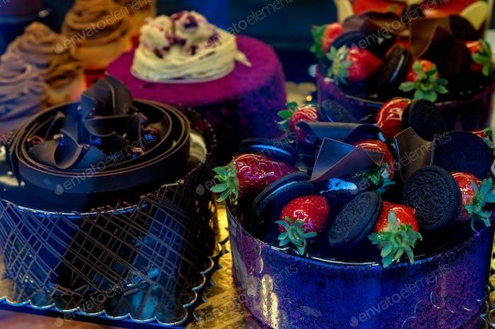 Pastelería con variedad de pasteles de chocolate con galletas y bayas