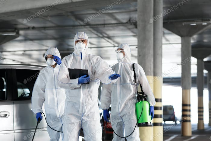 Virologists in protective suits on duty on public parking for first aid