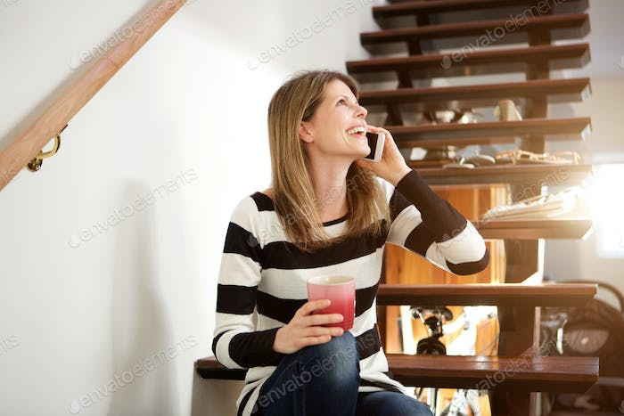beautiful woman sitting on stairs and making phone call