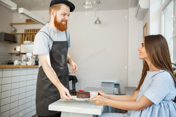 Coffee Business Concept - Waiter or bartender giving chocolate cake and talking with caucasian