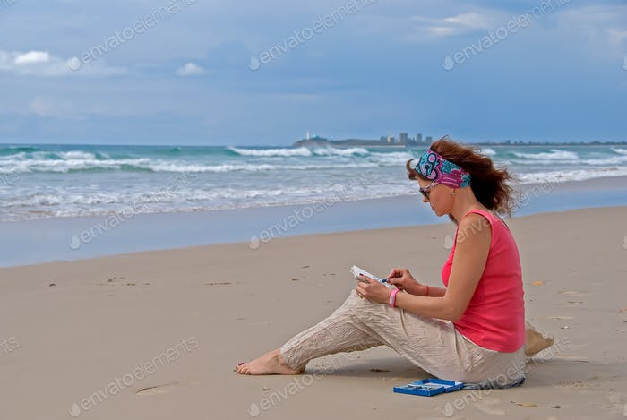 Woman sitting on the beach and drawing