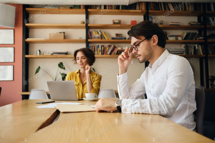 Handsome man in eyeglasses sitting at the table thoughtfully working with colleague in modern office