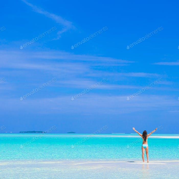 Junge glückliche Frau am weißen Sandstrand