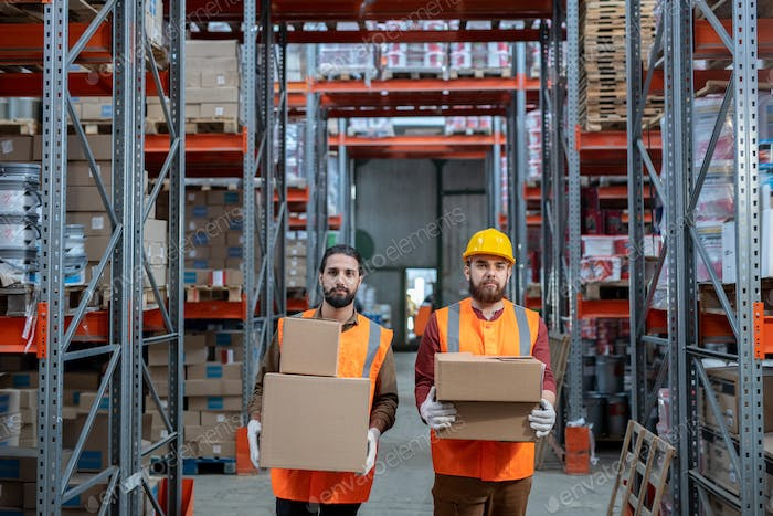 Movers in orange vests standing with boxes