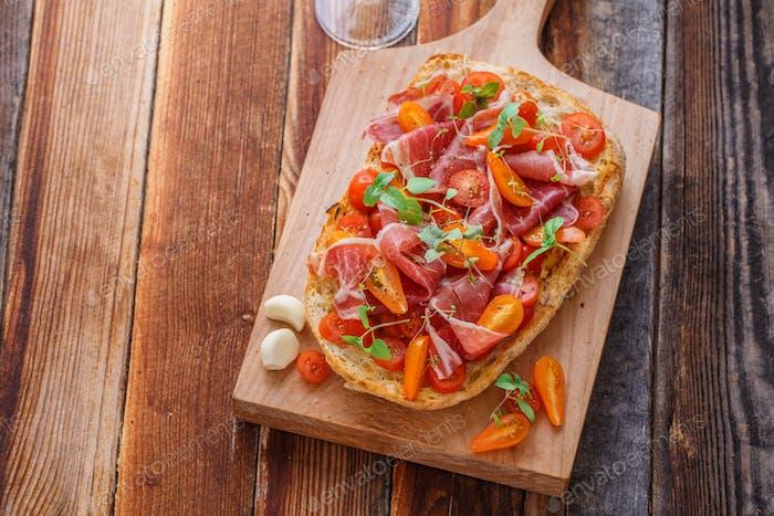 Italian bruschetta with wine on black cutting board, top view