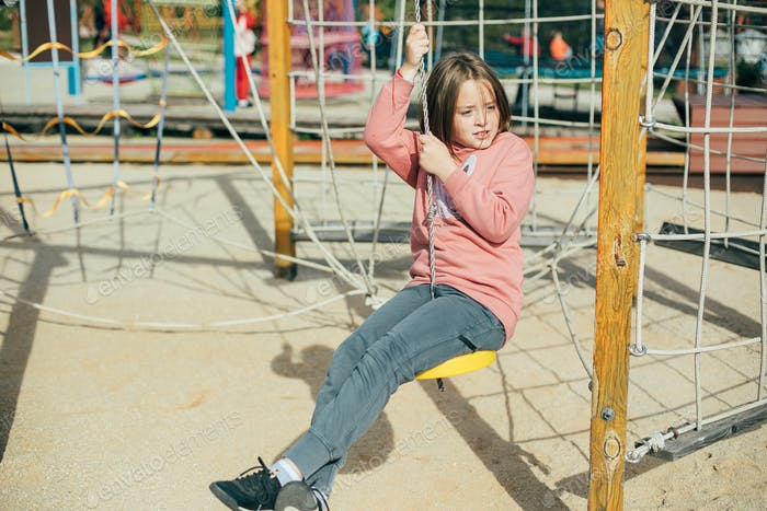 Cute caucasian girl 7-8 years old on playground. Outdoor activities, lifestyle, children's leisure