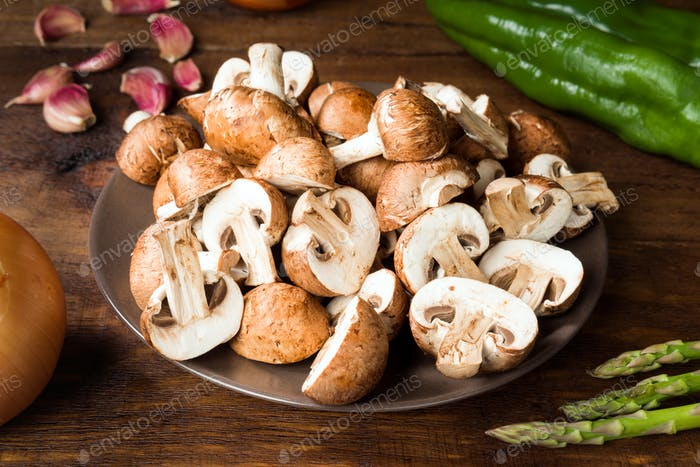 cut raw mushrooms and other ingredients on rustic wood