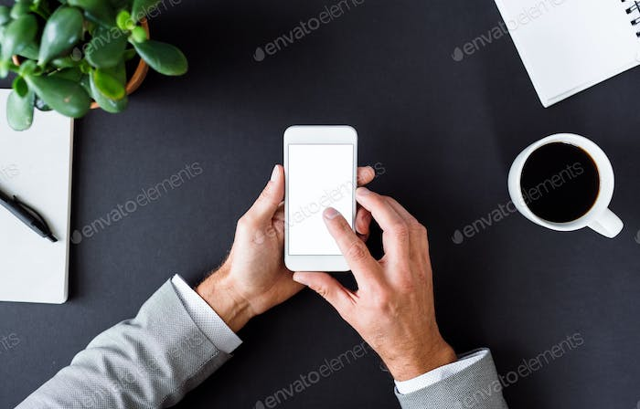 A midsection of businessman sitting at the table, using smartphone. A top view. Copy space.