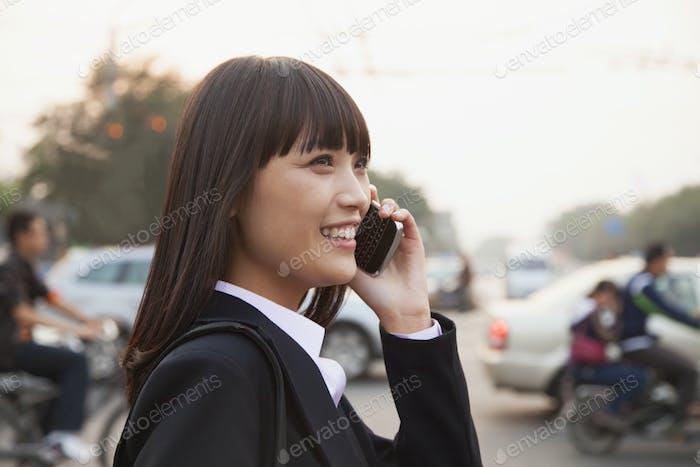 Junge Geschäftsfrau mit dem Telefon draußen auf der Straße in Peking