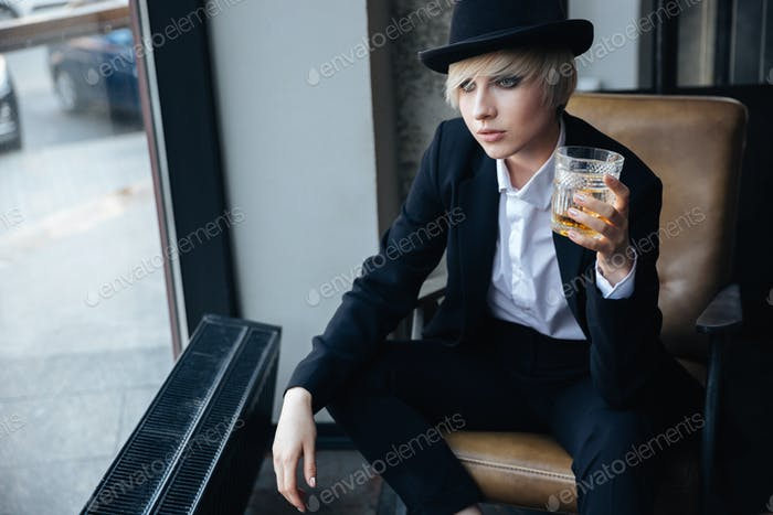 Stylish blonde girl in a hat holding glass in bar