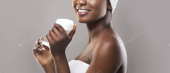 Black woman holding open jar of face cream in hands