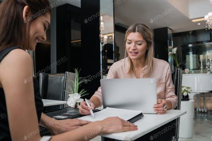 Zwei Geschäftsfrauen treffen sich in der Hotellobby.