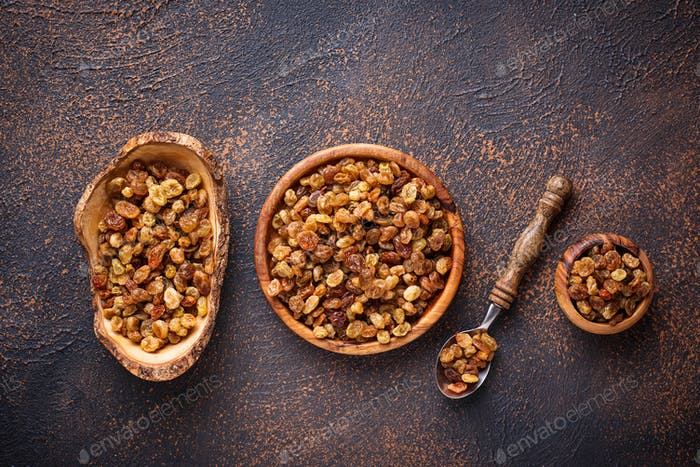 Raisins in wooden bowl on rusty background