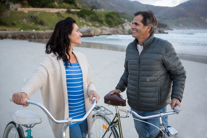 Couple standing with bicycle interacting with each other on beach