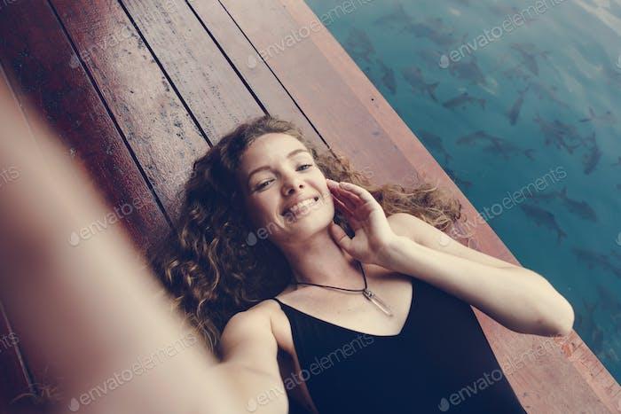 Frau entspannt auf einem hölzernen Steg