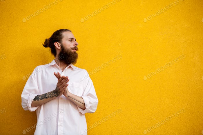 Cool bearded hipster on yellow wall