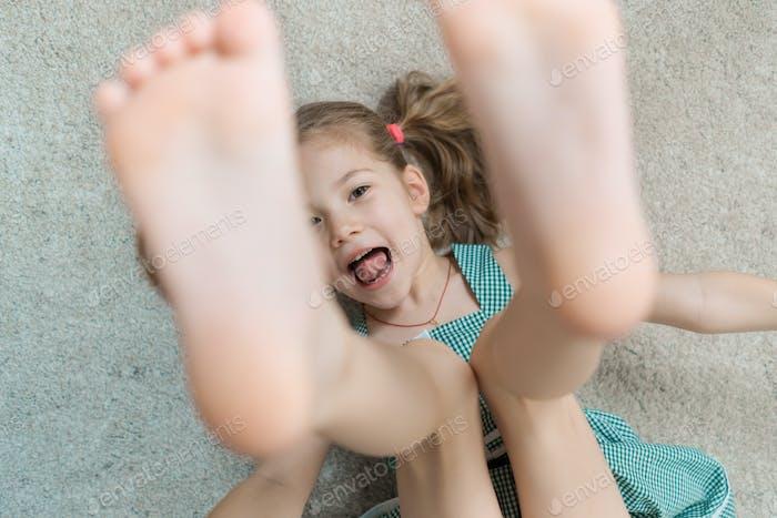 Расслабленная маленькая девочка, лежащая на полу в помещении и улыбающаяся