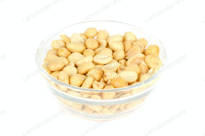 Roasted and salted peanuts in glass bowl over white