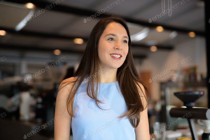 Glückliche junge Geschäftsfrau denken beim Blick durch das Fenster im Café
