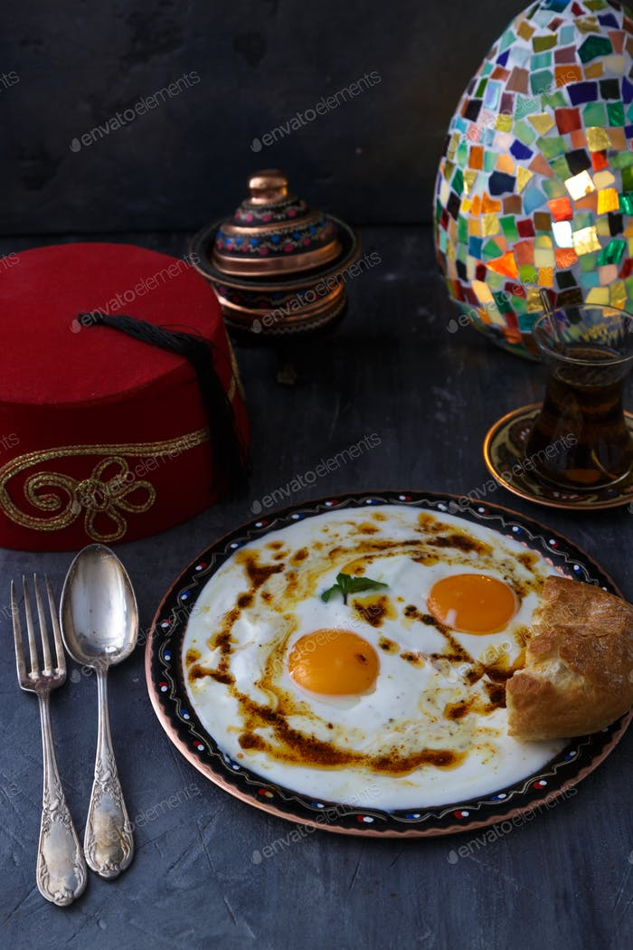 Cilbir, eggs in yogurt with spiced butter and herbs, served with bread and tea, turkish cuisine