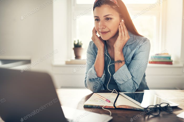 Employee woman with headphones looking at laptop in office