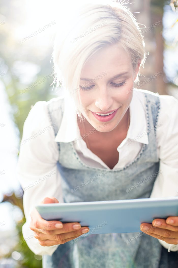 Pretty blonde woman using her tablet in the park