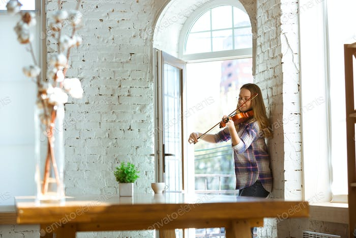 Young woman at home playing violin near opened window, improvising, quarantine lifestyle