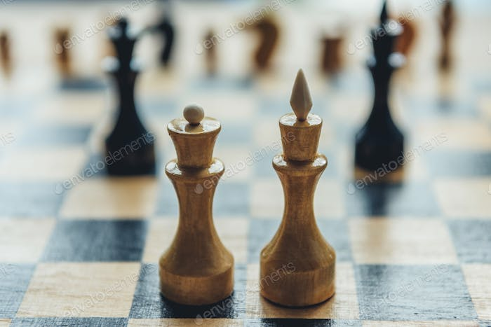 Closeup view of white chess king and queen figures on chess board