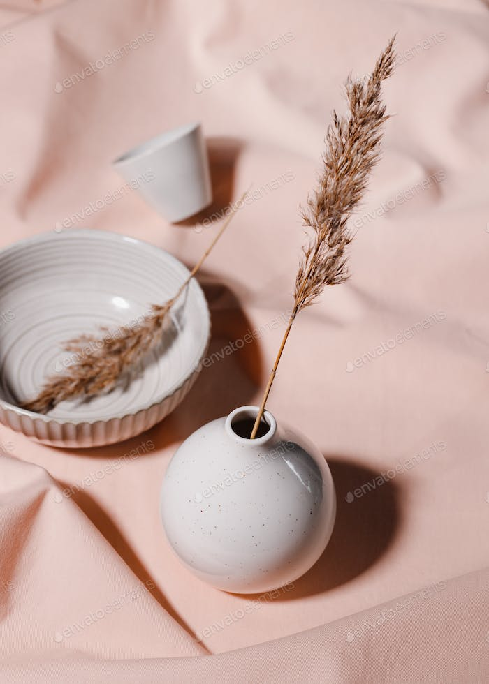 Abstract minimalist still life composition with ceramics and reeds over pink fabric.