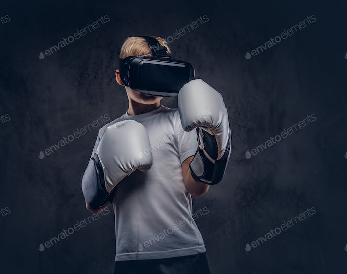 Schoolboy boxer wearing virtual reality glasses and boxing gloves, workout in a studio.