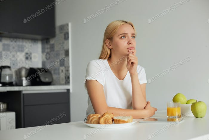 girl sits at the kitchen table, sad, looks thoughtfully to the window side