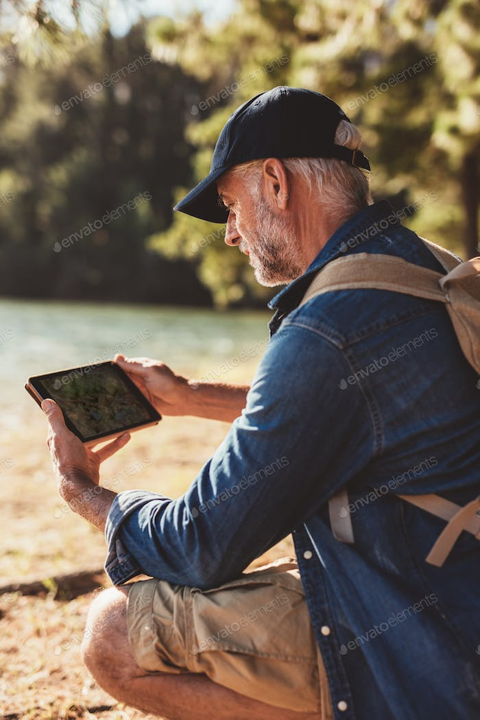Senior man using digital tab in the forest for navigation