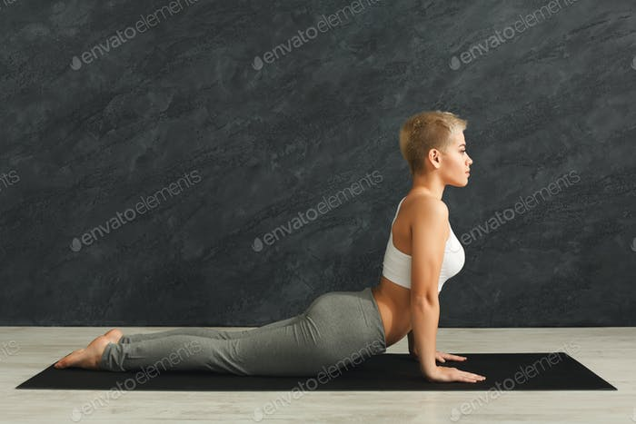 Woman training yoga in cobra pose.