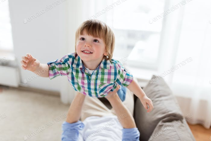 father hands holding happy little boy at home