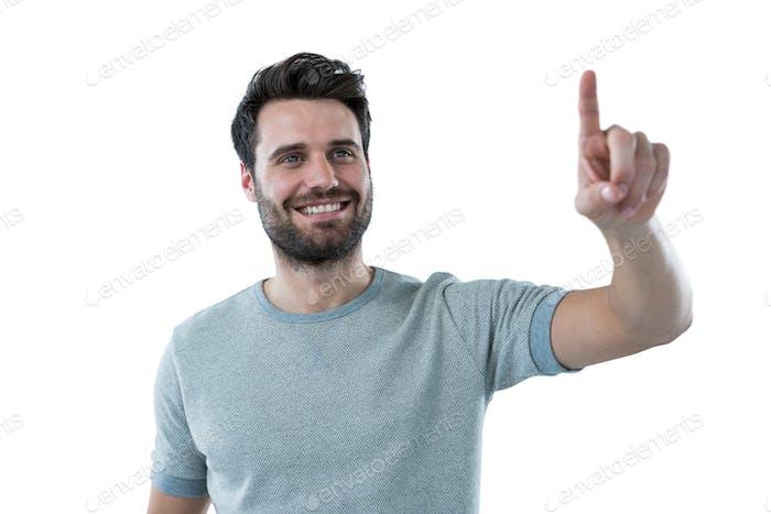 Lächelnder Mann, der vorgibt, einen unsichtbaren Bildschirm zu berühren