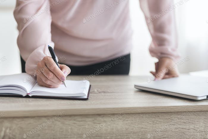 Senior business woman writing down tasks for working day
