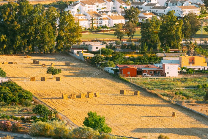 Andalusia region, Spain. Elevated View Of Rural Landscape Field With Hay Bales Rolls