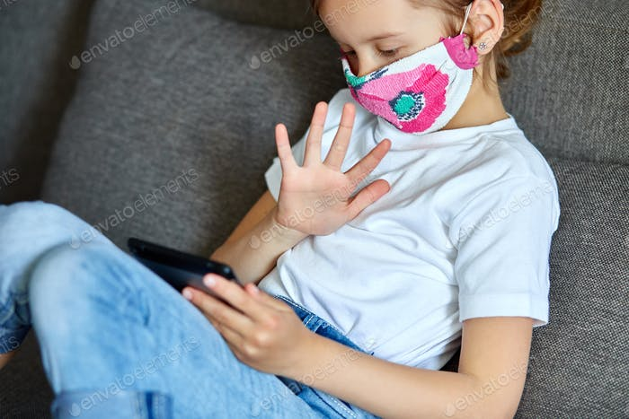 Little child girl in mask at home talk video with tablet meeting, online call friend