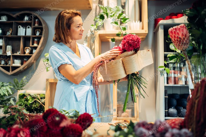 Female florist makes flower composition in shop