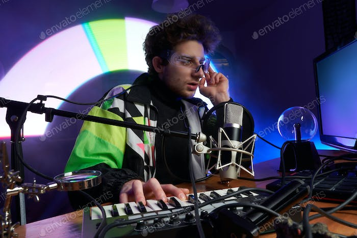 Caucasian composer mixing and playing music on his computer